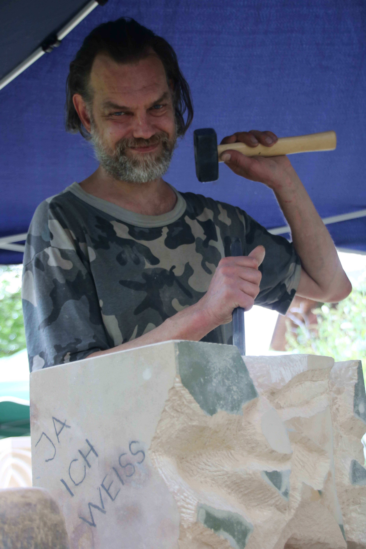 """Trott-war-Mitarbeiter bearbeitet einen Sandsteinquader mit Eisen und Fäustel, auf dem steht """"Ja, ich weiß"""""""